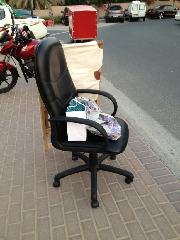 Chairs and a bag of loot from tje Arabian Ranches Community Market Day sitting at the curb waiting for TBG to pick us up!