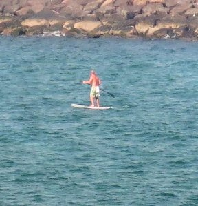 There's a guy paddleboarding!